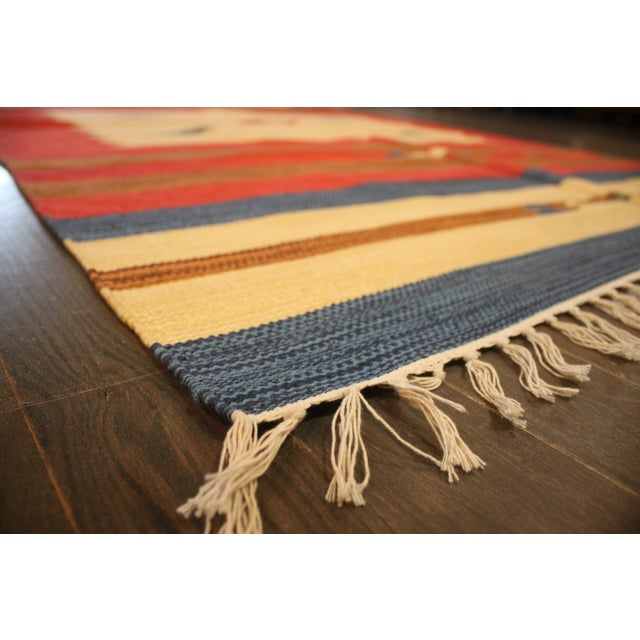 A hand-knotted multi-color Indian rug with an all over design. This gorgeous rug has magnificent detailing with multi-...