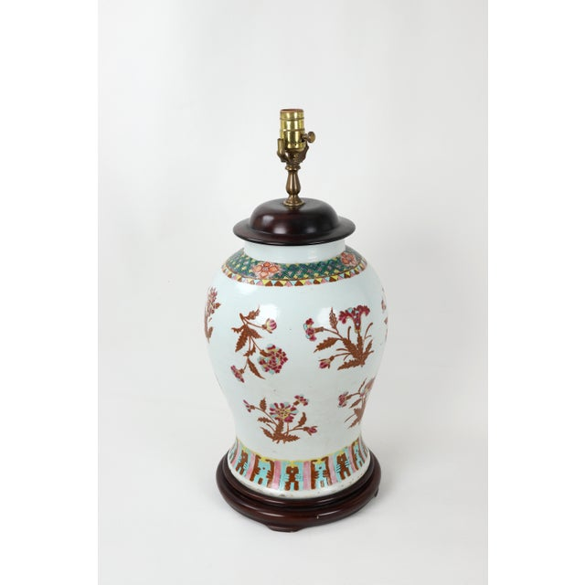 Temple jar lamp with copper tone leaves supporting famille rose flowers. The top is decorated in a net of green and small...