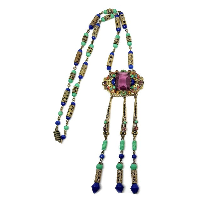 Circa 1920s to 1930s Czechoslovakian Egyptian Revival necklace with a brass pendant set with a large emerald cut, purple...