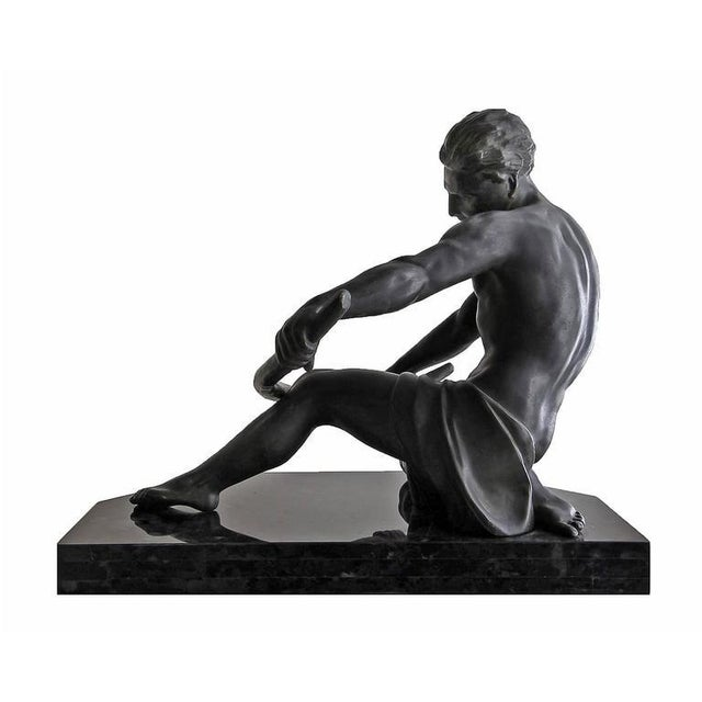 This large and impressive sculpture (21 x 18 x 15 inches) is the height of Art Deco style. It depicts a semi-nude man...