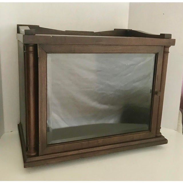 Here is a wonderful wood display case with a beveled glass, swing open door! As you can see, it has a bit of greek revival...