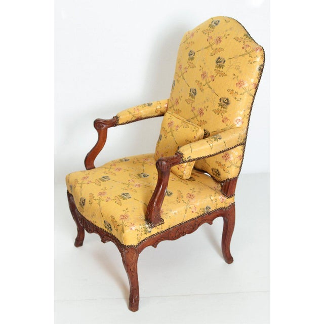 A Louis XV carved walnut armchair with peg construction and finely carved scroll arms. The chair rest on cabriolet legs...