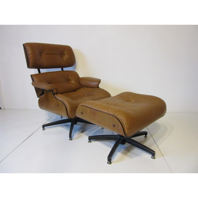 A saddle colored soft and rich lounge chair with matching ottoman in the style of Herman Miller and Eames. Cast aluminum...