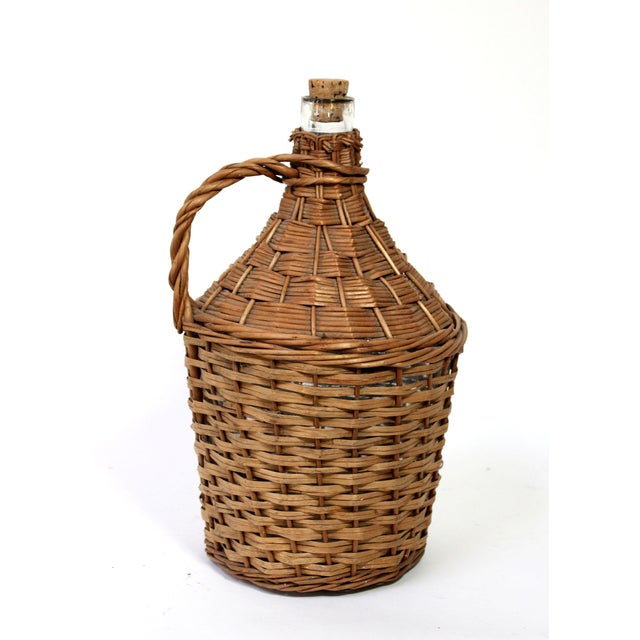 Antique thick clear glass wine jug with original cork stopper, covered in hand-woven wicker with handle. Origin of...