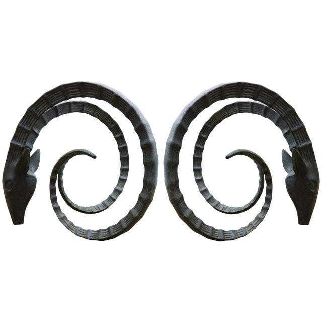 Iconic, sculptural pair of iron Ibex or ram's head table bases with the large curved horns and intricate detailing....