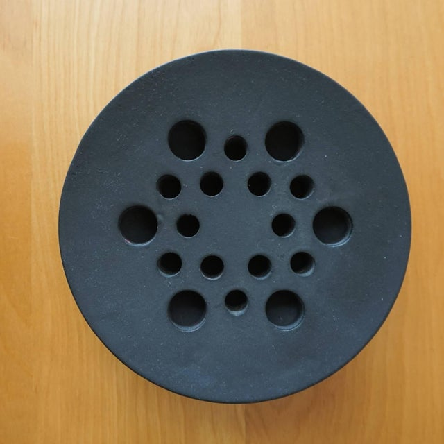 A 1960s cast iron tripod candle holder, designed by Jens Quistgaard for Dansk. Signed in the metal.
