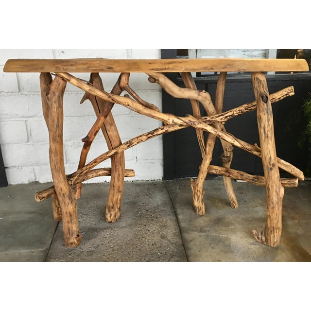 Live edge top with a branch base console with copper twine wrapped within. Made in the 2000s.