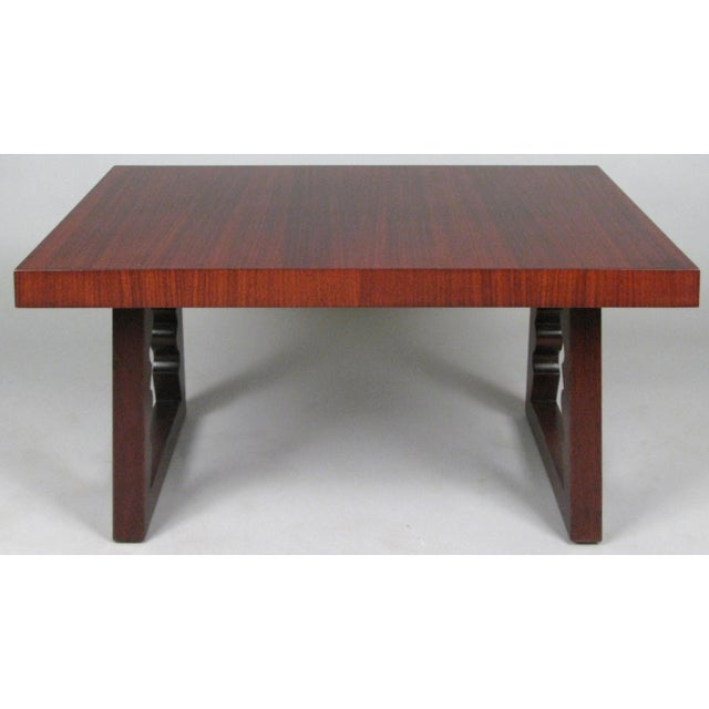 A beautifully detailed rosewood cocktail table designed by Andrew Szoeke, circa 1948. With a rectangular top and mahogany...
