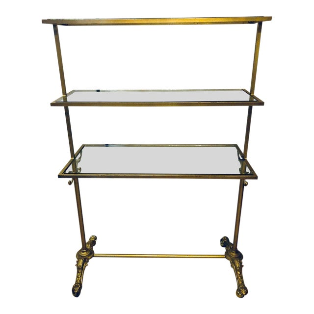 A Hollywood Regency three-tier large bakers rack gilt metal and glass shelves. A large and impressive bakers rack that is...