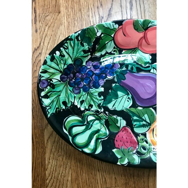 """With a colorful pattern on a rich black ground, this 19"""" oval serving platter is signed by Mississippi pottery artist..."""