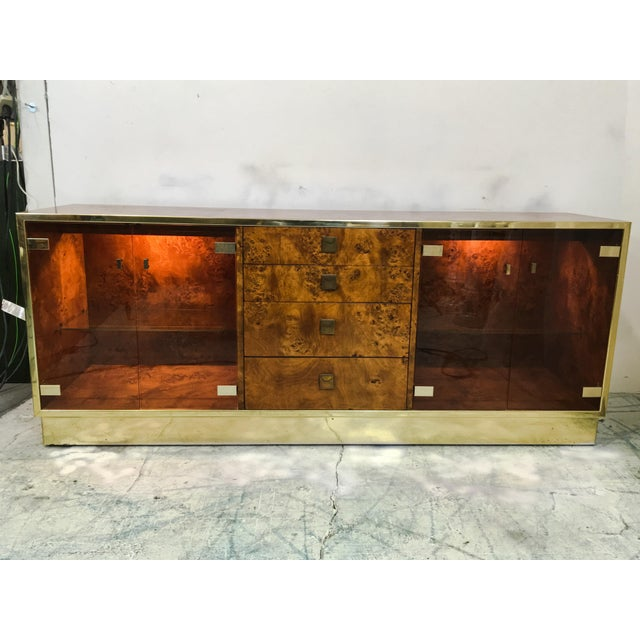 1970s brass and burl credenza manufactured by Founders. The left and right sides are illuminated by 40 watt bulbs and have...