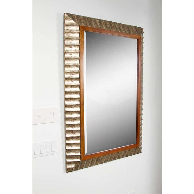 An elegant beveled mirror with a thin cherry inner frame held within a wide fluted and beveled frame in a glamorous silver...