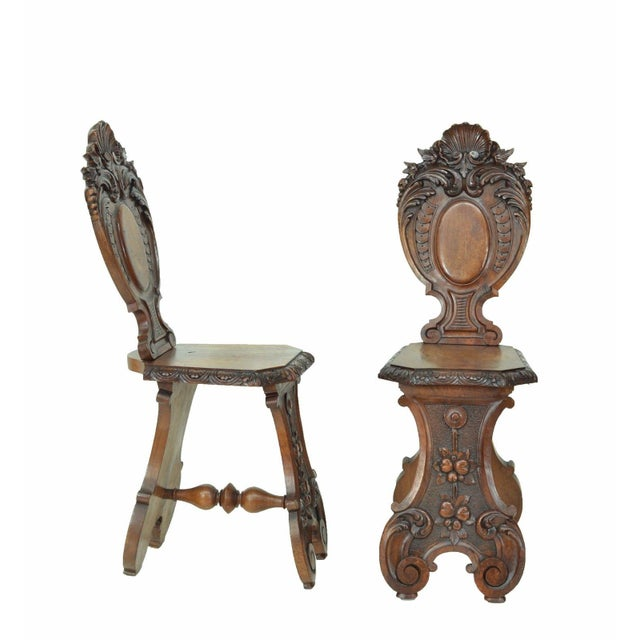 A beautiful pair of Italian antique side chairs features detailed carvings,  shaped back and base - Italian Antique Carved Renaissance Revival Side Chairs - A Pair