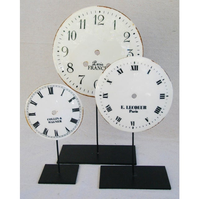 """Set of three decorative porcelain on metal clock face dials with metal stands. Not antique. Minor age wear. Largest: 8""""..."""