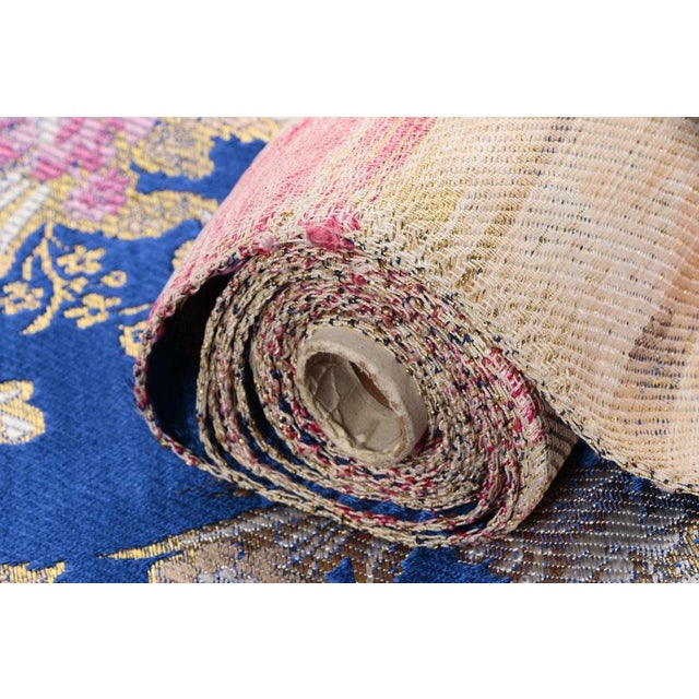 A luxurious gold embroidered silk brocade textile bolt. Jacquard Floral Fabric in blue and pink with Golden Metallic...