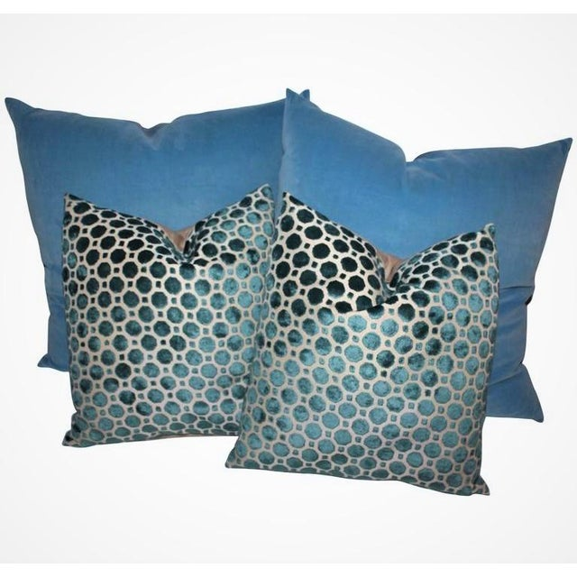 The two in the front are patterned teal green/blue pillows with tan cotton linen backing. The back pillows are in a robin...