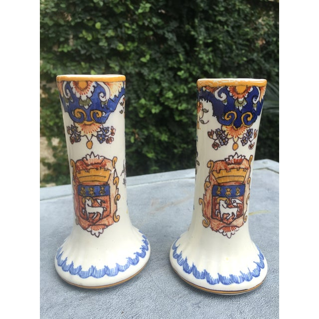 Pair of antique French faience Rouen vases. Hand painted floral design with a Coat of Arms on one side. and foliage...
