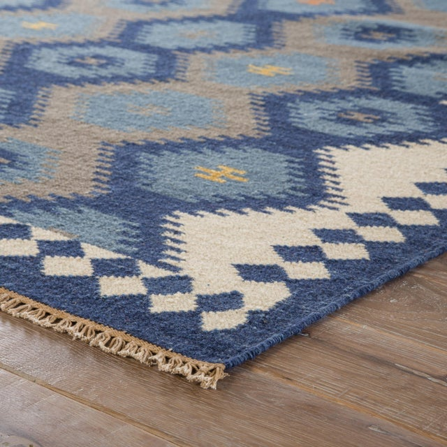 This traditional-style Kilim area rug boasts a tile-inspired design in a contemporary blue and navy colorway. The...