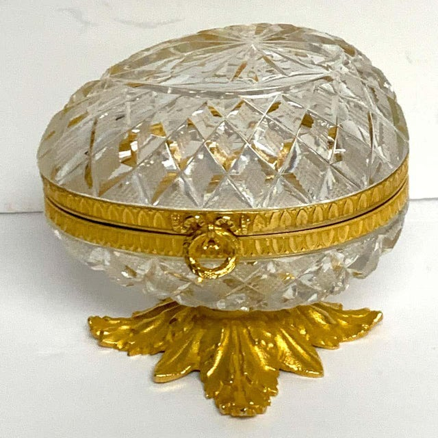 "Baccarat style cut glass and ormolu egg motif box, unusual shape. No flaws observed ready to place. Raised on a 3.5""..."