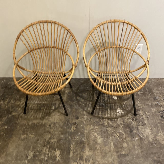 Pair of mid century rattan chairs from Belgium. Great modern shape fun pair of decorative chairs.