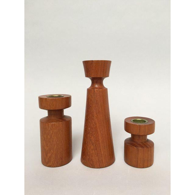 Assembled collection of three danish teak turned wood candle holders in complementary shapes. The tallest measures about...
