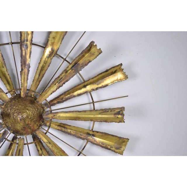 Tortured brass finish on a crafted metal wall sculpture combining torch but brass, heavy brass wire and a figured center....
