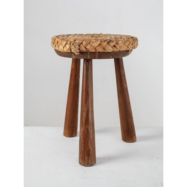 """A French stool made of wood with a woven rope seating (34 cm/13.5"""" diameter) and three round, tapering legs. The stool is..."""