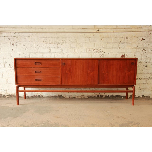 Mengel Furniture Co. Offering a gorgeous Mid-Century Danish Modern teak long credenza. The credenza features beautiful...