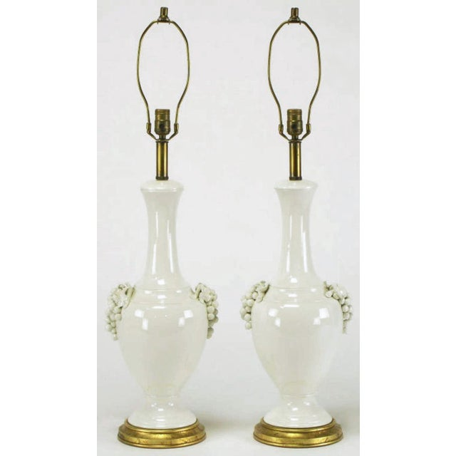 Elegant and early pair of urn form white ceramic table lamps with grape cluster handles from Frederick Cooper Studios....