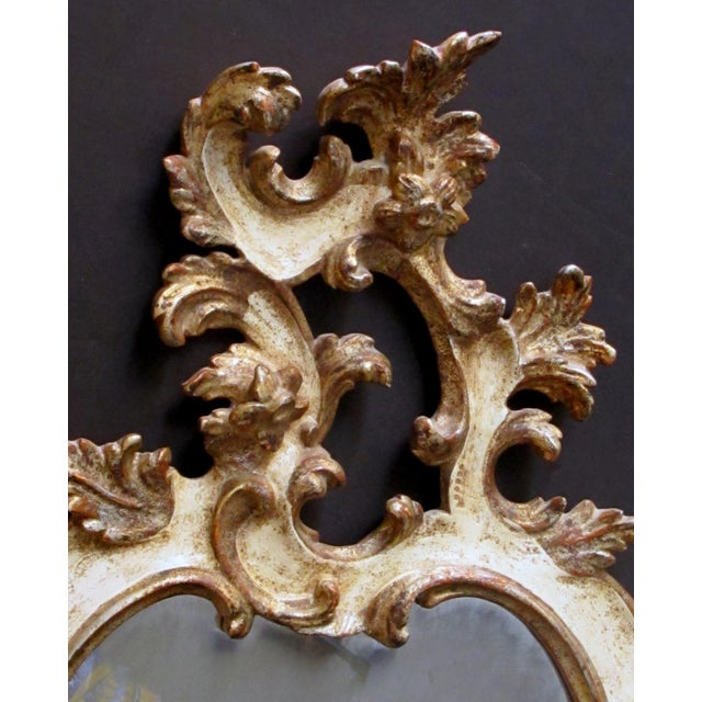 the exuberantly carved mirror with openwork asymmetrical crest above a cartouche-shaped body all adorned with foliate and...
