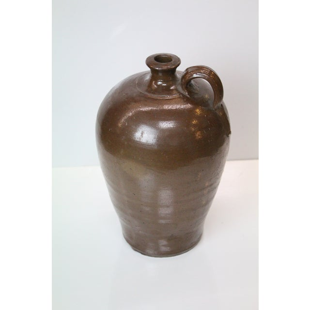 Brown glazed and painted jug unknown maker.