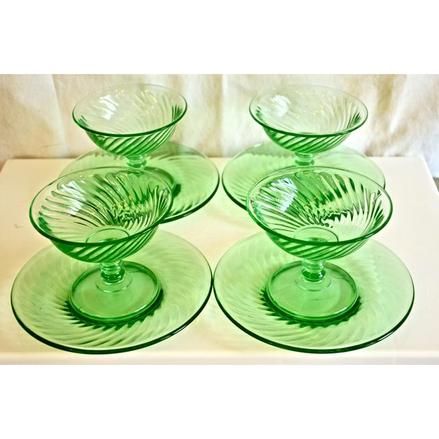 Set of four vintage bright green glass stemmed dessert coupes with saucers in a swirl pattern, circa 1940. Fluoresce in...