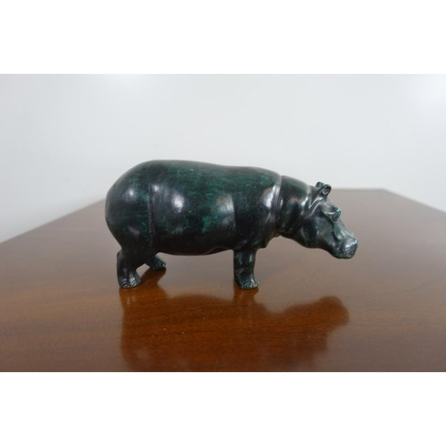 This bronze hippo sculpture is by Sergio Bustamante and is signed and numbered 10/100. There is a coating over the piece...