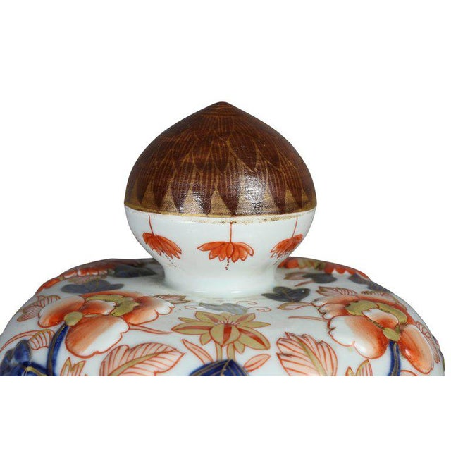 Each with finial and domed covers and baluster body. Raised decoration in the Imari pattern.