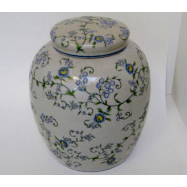 Gray crackle glaze ceramic ginger jar with hand-painted soft blue and yellow flowers on green flowing vines with leaves....