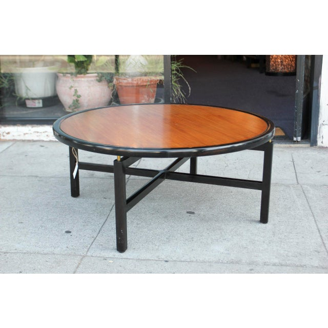 Stunning round black lacquered base, and wood top round coffee table. The table was made by the king of furniture Baker...