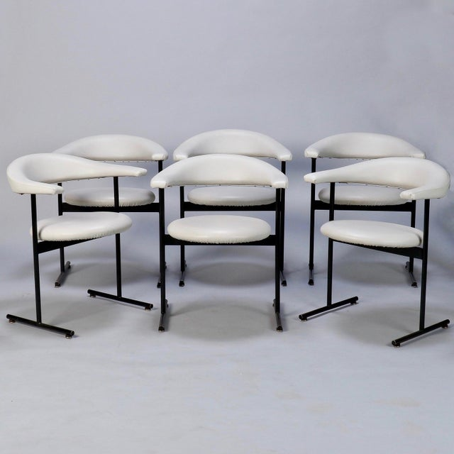 Set of six industrial inspired mid century armchairs. Sleek, streamlined seats and back rests with black metal floating...