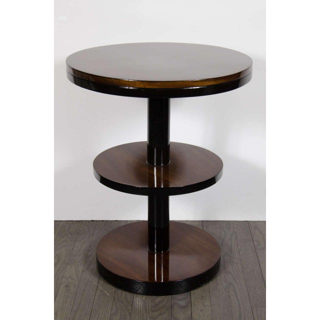 This streamline pair of Art Deco occasional tables feature a three-tier design and column form in bookmatched walnut and...