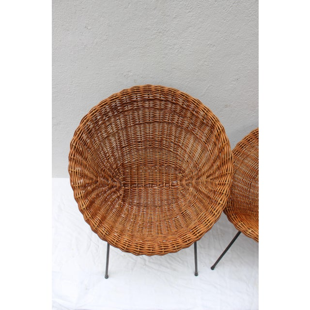 """Set of two Italian rattan chairs and table in the style of Franco Albini. Measures: Chairs 29.5"""" H x 27.5"""" W x 25"""" D x 15""""..."""