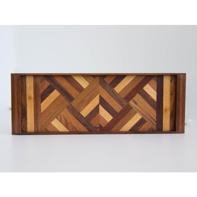 A narrow serving tray by Don Shoemaker for Senal of Mexico. The tray has a rosewood frame with integrated handles at...