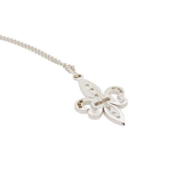 A fine elegant and Vintage pendant in the form of a Fleur-De-Lis. The pendant is set with 21 small diamonds,...