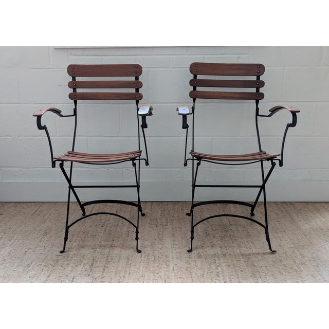 An exquisite pair of iron and teak vintage garden / patio chairs. These French café style chairs have beautiful curving...