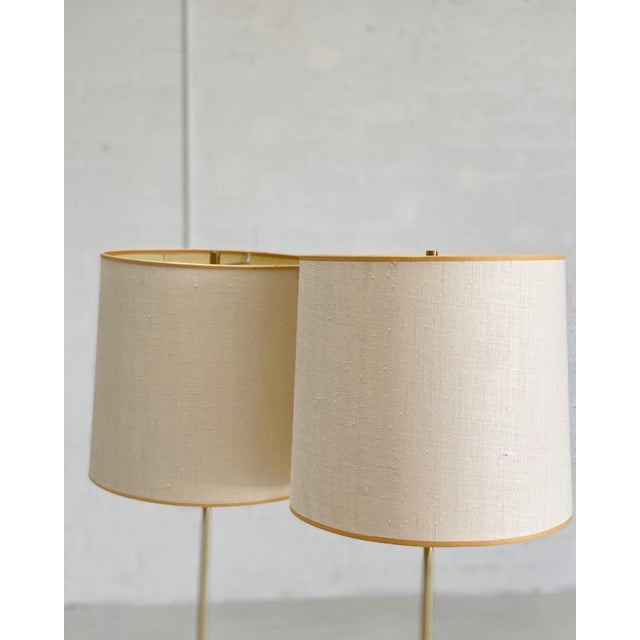 Pair of mid-century brass floor lamps with shades with lovely geometric brass base, and feminine silhouette. Designed by...