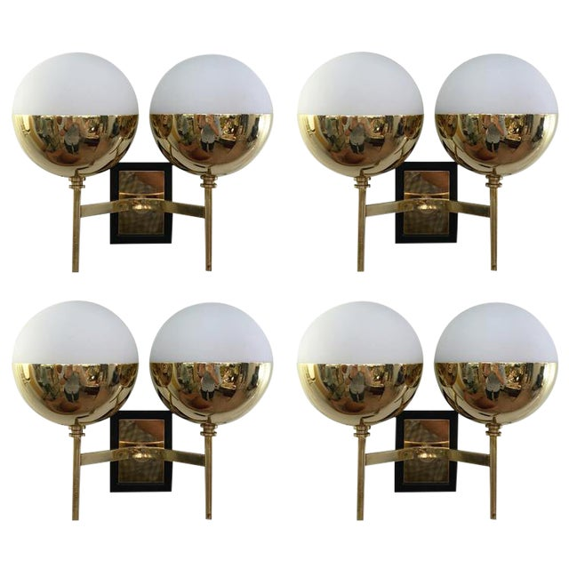 Set of four diminutive wall lights in the manner of Stilnovo each featuring two frosted glass shades on a brass frame. The...