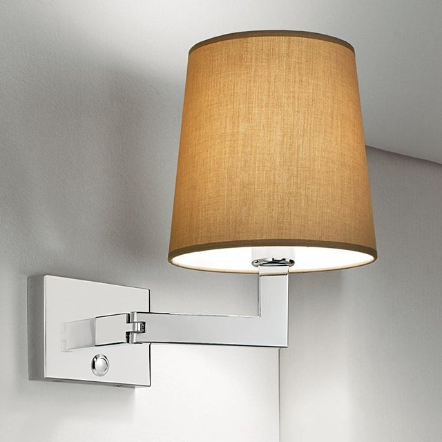 Polished chrome wall lamp with robust detailed hinges that allow arm to swivel. Also available in Antique Brass (AB)....