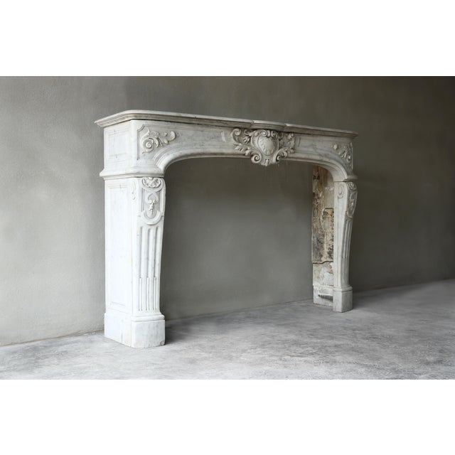 Exclusive marble antique fireplace from the era of Louis XIV of white Carrara marble. This decorated fireplace dates back...