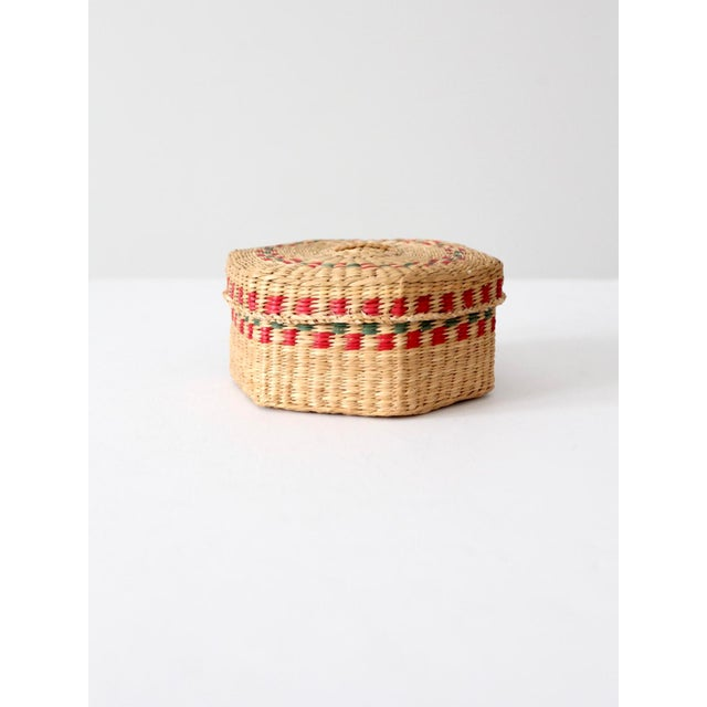 This is a vintage sweetgrass basket. Colorful red and green patterns detail the small, hand-woven natural basket. The...