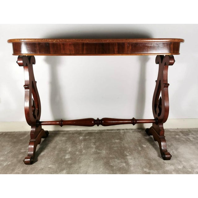 Danish coffee table (or writing desk) in light mahogany, the top with rounded corners is supported by two elegant legs in...