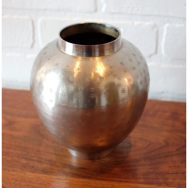 Vintage metal vessel with hand hammered exterior.
