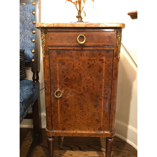 From the Rochelle region of France. A marble top with marquetry inlay wood and brass accents. Inside the door is one...